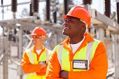 picture of substation  - smiling african electrical engineer in substation with colleague on background - JPG