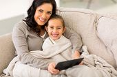 pic of snuggle  - happy woman and her little daughter snuggle on couch wrapped with blanket - JPG