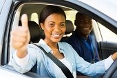 stock photo of seatbelt  - beautiful female african learner driver with instructor giving thumb up - JPG