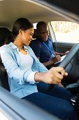 picture of seatbelt  - smiling young african girl taking lessons from driving instructor  - JPG