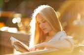 foto of beatitudes  - Happy blonde girl sitting and reading a book - JPG
