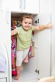 picture of wardrobe  - Little girl playing and hiding inside wardrobe