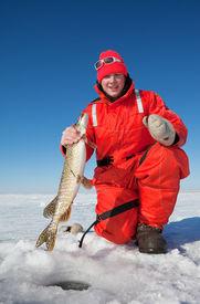 foto of ice fishing  - Happy ice fisherman holding a northern pike - JPG