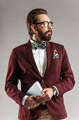 image of bow tie hair  - Portrait of beautiful stylish young bearded man in a burgundy jacket and bow tie with book in hand - JPG
