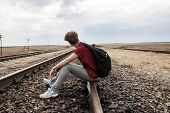 picture of depressed teen  - Teen girl with problems sittingon old rail road - JPG