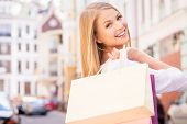 stock photo of cheer  - Rear view of beautiful young cheerful woman holding shopping bags and looking over shoulder while standing outdoors - JPG
