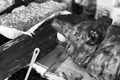 pic of spit-roast  - Black and White image of person and Roast Pork at Street Market