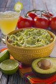 picture of avocado  - home-made guacamole with avocado,limes,tomatoes, and margarita set against a wood surface