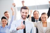 foto of thumb  - Happy businessman showing his thumb up and smiling while his colleagues standing in the background - JPG