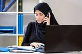 stock photo of arabic woman  - Arab businesswoman watching documents and being on the phone - JPG