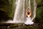picture of waterfalls  - young woman doing yoga in a forest near waterfall - JPG
