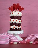 stock photo of red velvet cake  - Novelty triple layer red velvet cupcake on white cake stand with ribbons and candy against a vintage shabby chic pink and red wood background vertical - JPG
