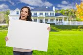 image of exciting  - Excited Mixed Race Female with Blank Sign In Front of Beautiful House - JPG