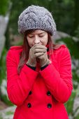 stock photo of overcoats  - Young woman shivering with cold and blowing hot air to the hands on a forest wearing a red overcoat - JPG