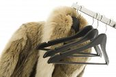 stock photo of coat  - Coat hangers and a luxurious fur coat hanging on a metal clothing rail close up view over white - JPG