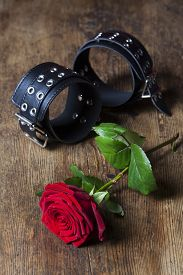 picture of leather-bound  - leather cuffs with a rose on dark wood - JPG
