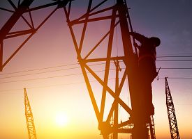 image of substation  - Worker at an electric substation with sunset background - JPG