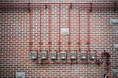 picture of lng  - Row of residential natural gas meters and pipe on brick wall - JPG