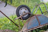 picture of wheelbarrow  - An old rusty blue wheelbarrow lying upside down in overgrown grass - JPG
