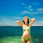 stock photo of maternity  - Smiling Pregnant Woman with Hands behind Head Sunbathing by the Sea - JPG