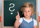 image of clever  - clever girl in front of black board with forefinger up - JPG