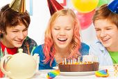 picture of teen smoking  - Beautiful young teen girl laughing at her birthday party blowing candles on a cake with happy friends around - JPG