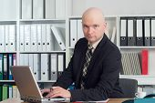 stock photo of bald head  - young businessman with bald head in the office is looking in to the camera - JPG