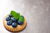 picture of curd  - Shortbread home made tartlet filled with lime curd and blueberries on old vintage metal background - JPG