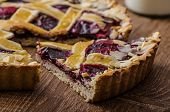 stock photo of tarts  - Shortbread tart with cherries with beautiful grid sprinkled with almonds - JPG