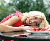 stock photo of strawberry blonde  - Blonde beautiful girl laughing eating and playing with fresh strawberry - JPG