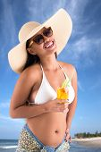 stock photo of filipina  - Sensual woman in hat holding cocktail and smiling - JPG