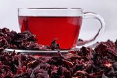 image of hibiscus  - Cup of hibiscus tea in a heap of dried petals of hibiscus  - JPG