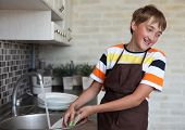 pic of homemaker  - boy doing the dishes in the kitchen - JPG