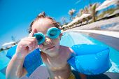 pic of goggles  - Cute boy in swimming armbands and goggles looking at the camera - JPG