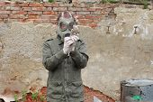 picture of nuclear disaster  - Man with gas mask and green military clothes explores dead bird after chemical disaster - JPG