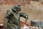 stock photo of gas mask  - Man with gas mask and green military clothes explores dead bird after chemical disaster - JPG