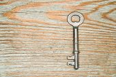 stock photo of hasp  - Vintage key from the lock on a wooden texture - JPG