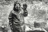 image of gas mask  - Man with gas mask and green military clothes explores dead bird after chemical disaster - JPG
