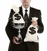 stock photo of money prize  - businessman holding trophy and money bags isolated on a white background - JPG