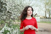 foto of daydreaming  - Daydreaming attractive brunette girl at spring fruit tree in white bloom - JPG