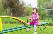 foto of seesaw  - Little cute girl sits on seesaw in a sunny day - JPG