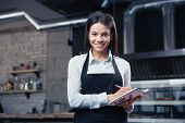 picture of apron  - Happy charming female waiter in apron writing order and looking at camera - JPG