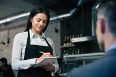 pic of apron  - Female waiter in apron writing order in restaurant - JPG
