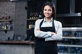 image of apron  - Happy pretty female waiter in apron standing with arms folded in cafe and looking at camera - JPG