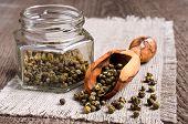 stock photo of peppercorns  - Green peppercorns in wooden scoop on burlap - JPG
