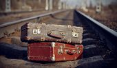 pic of old suitcase  - The image of two old vintage suitcases on railway tracks - JPG
