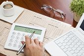 stock photo of anal  - Analizing fiancial data with economy newspaper and calculator - JPG