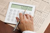 stock photo of anal  - Analizing economic data with calculator on table - JPG