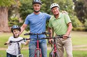 picture of multi-generation  - Happy multi generation family on their bike at the park on a sunny day - JPG