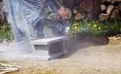 picture of bricklayer  - Bricklayer cutting a brick with circular saw - JPG
